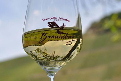 Weinberge spiegeln sich in Brauneberg an der Mosel in einem Glas Riesling.